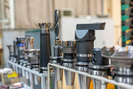 Arbors with cutters and drills for a CNC machine on a rack, tools and equipment in a factory and an enterprise. Imagens