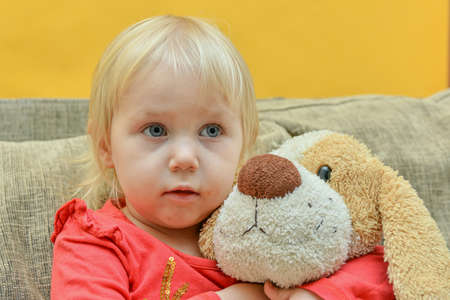 A little girl hugs a soft toy and watches tv