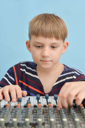 A boy controls a mixing console in a music studio.