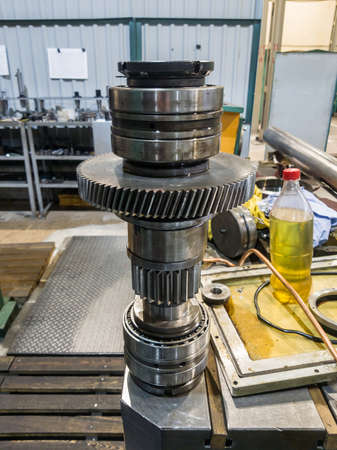 Shaft with bearings and gears from a disassembled gearbox for repair.