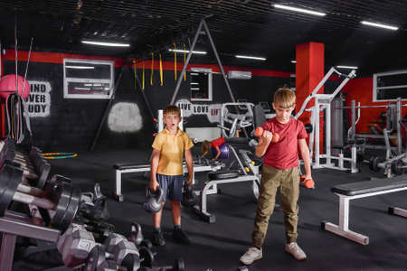 Two boys are engaged in the gym with dumbbells and weights.