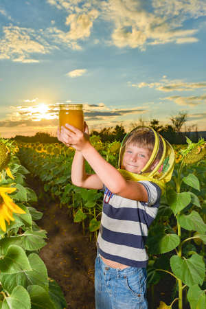 boy with honey in a field of sunflowers against the backdrop of the evening sun.