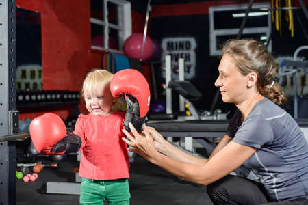 Mom the trainer helps the little girl put on boxing gloves.