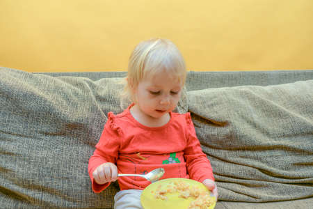 A little hungry girl eats porridge from a plate while sitting on the couch and watches children TV programs on TV. Imagens