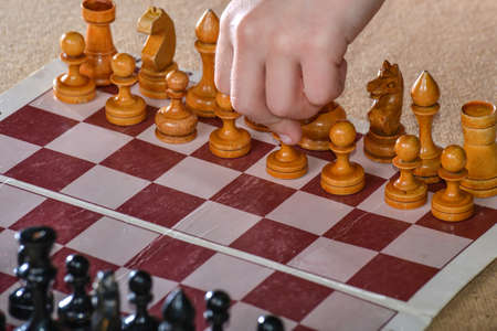 The player holds a white pawn in his hand and starts the game of chess.