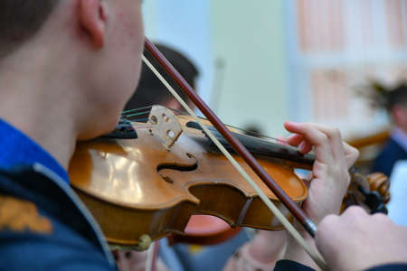 A young musician plays the violin in a symphony orchestra.