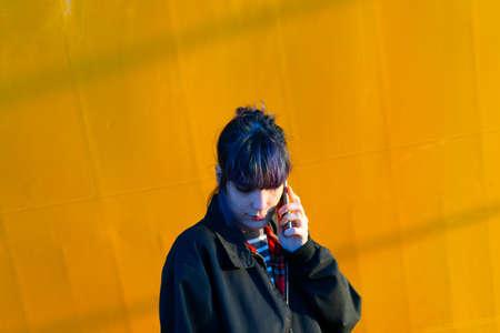 Alternative girl in yellow background talking smart phone