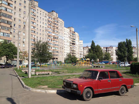 Apartment buildings and old soviet era red car at Krivoy Rog center Ukraine