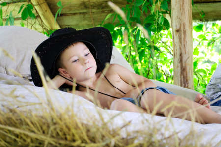 boy in a cowboy hat is in the hayloft photo