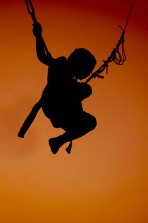 bungee jumping: silueta de un ni�o saltando sobre el bungee en el atardecer naranja Foto de archivo