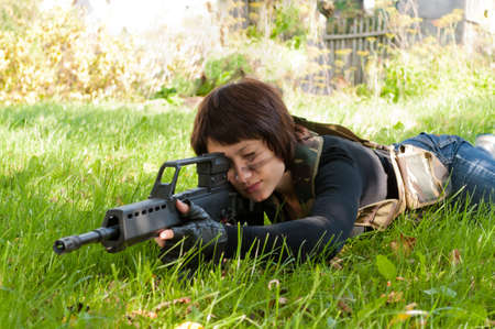airsoft: beautiful girl with a gun to airsoft outdoors