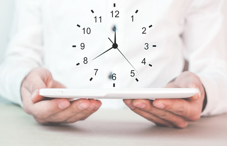 Businessman holding clock. Concept of saving time.