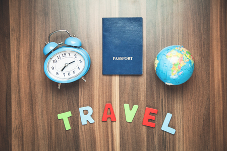 Colorful word travel alarm clock with passport and globe on the wood background.