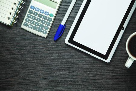 Digital tablet, calculator, pen, coffee and notepad on dark wood background.  Business concept Standard-Bild