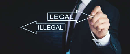 Man writing Illegal and Legal words with arrows on screen.