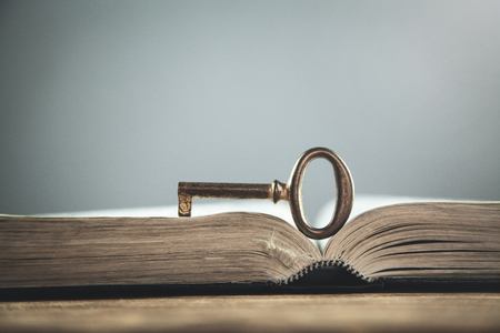 Old key on bible. Concept of wisdom and knowledge