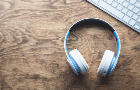 White wireless headphones and computer keyboard on wooden desk.