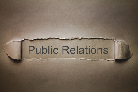 Public Relations text on torn paper.
