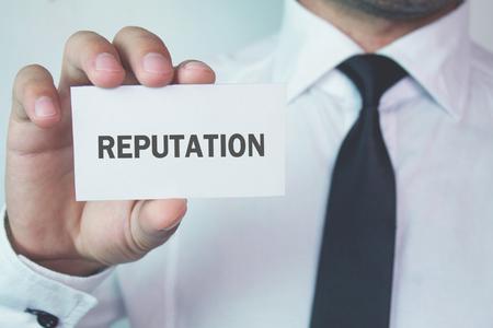 Hombre de negocios que muestra la reputación de la palabra en la tarjeta de visita.