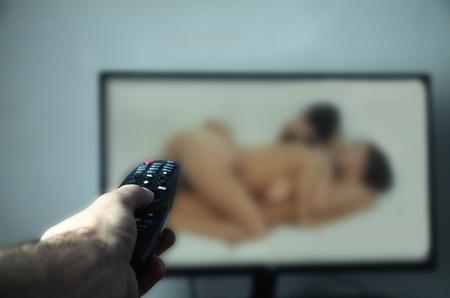 Main tenant la télécommande du téléviseur. En train de regarder