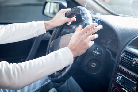 Man smoking a cigarette at the wheel of a car. Driving and smoking Фото со стока