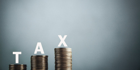 Word Tax with coins. Tax Concept
