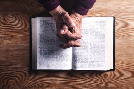 Hands of elderly woman praying. Religion concept