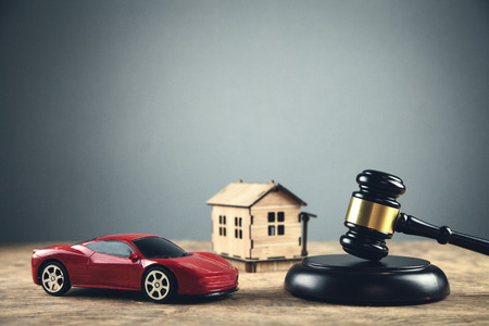 Wooden judge gavel with house and car. Auction and bidding concept