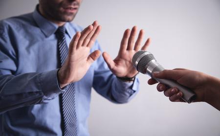 Businessman doing stop gesture. Reporter