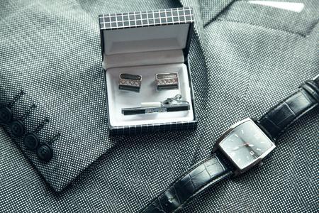 Cufflinks with wristwatch in suit background.