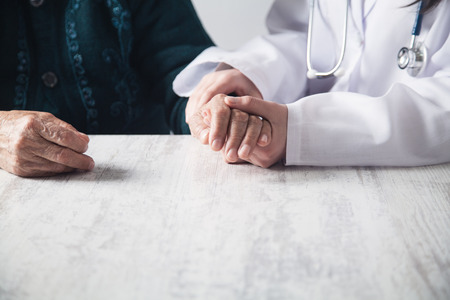 Doctor holding patient hands in hospital. Patient care