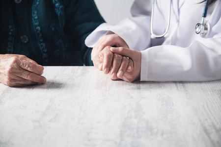 Doctor holding patient hands in hospital. Patient care 写真素材 - 121298713