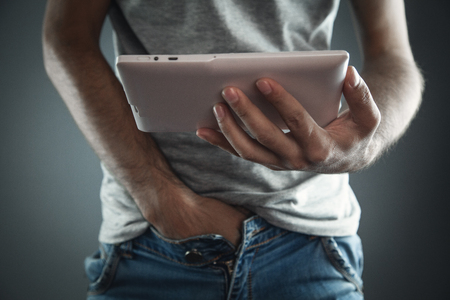 Man watches adult video on tablet. Concept of porn,