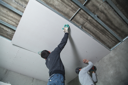 Workers fitting panel into frame of ceiling. Standard-Bild - 122610072