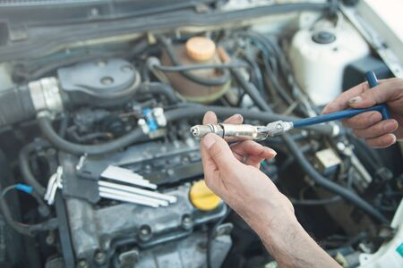 Technician installing new candle in car engine. Фото со стока