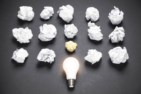 Light bulb and crumpled papers in the black background. Idea
