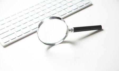 컴퓨터 키보드가 있는 돋보기. 인터넷 검색
