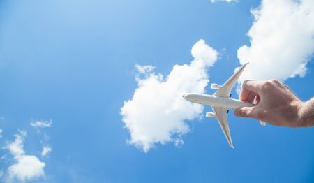 Hand holding airplane model in front of blue sky background. Travel Zdjęcie Seryjne