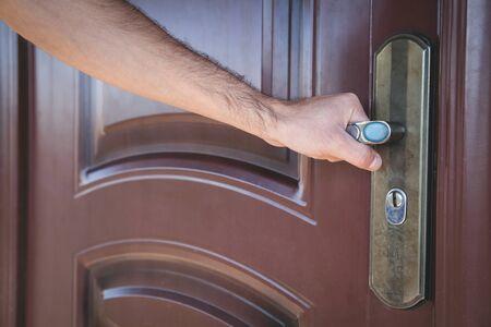Hand holding a metal handle in the door.