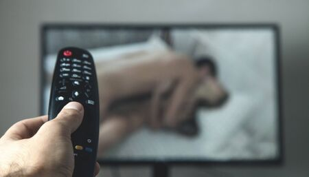 Hand holding TV remote controller. Watching porn