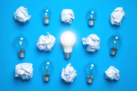 Light bulb and crumpled papers in the blue background. Idea