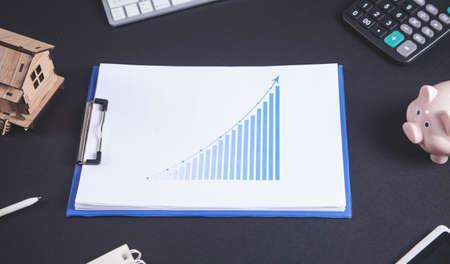Wooden house model with financial chart. Zdjęcie Seryjne