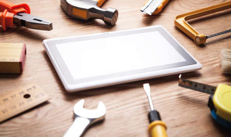 Work tools with a tablet on wooden background.