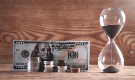 Hourglass and money on a wooden background. Zdjęcie Seryjne