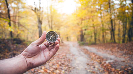 Male hand holding compass in autumn forest.