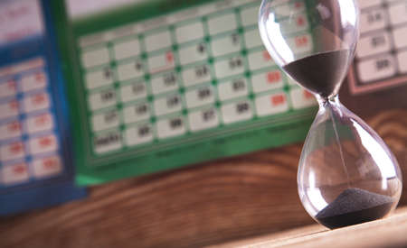 Hourglass on the wooden table in calendar background. Deadline concept