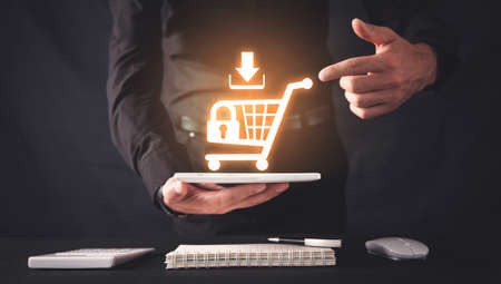 Businessman holding a tablet with a shopping cart. Shopping security. Online shopping