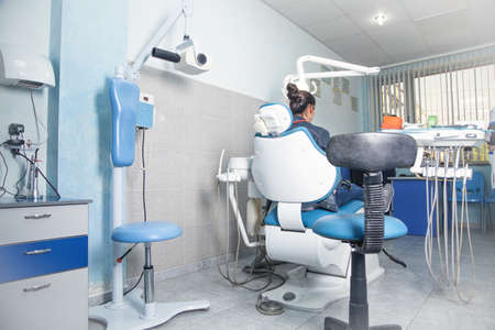 Woman sitting in a dental chair in the clinic.