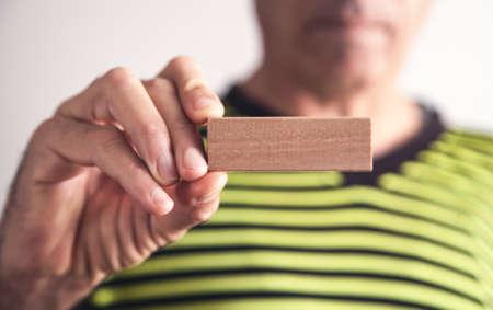 Man holding wooden empty block.