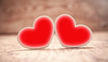Wooden red hearts on wooden table.